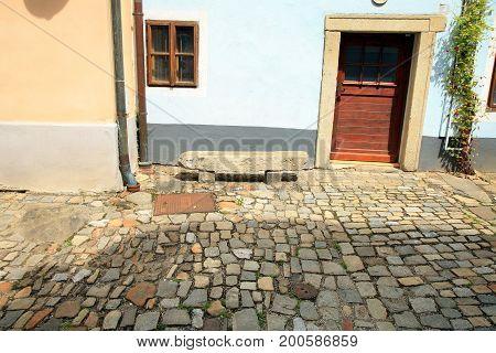 A stone bench on a cobbled street. Tranquility courtyard in Cesky Krumlov, Czechia, Czech Republic.