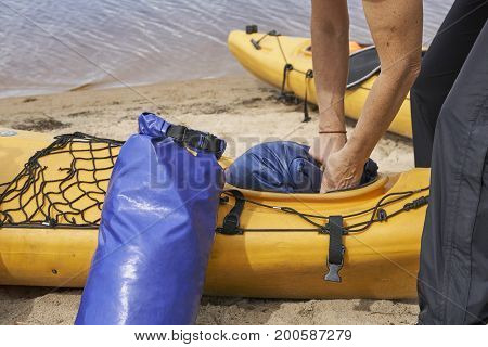 Hands of a female hiker inserting a waterproof bag with the things into the kayak
