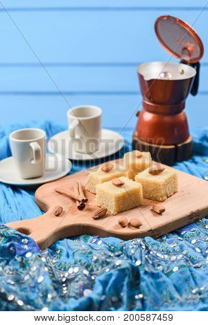 Homemade halava traditional Indian sweetmeats served with coffee on bright blue embroidered cloth side view with copyspace