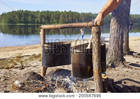 Hikers preparing breakfast on the fire on the riverside in sunny morning