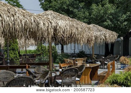View of cosy nook for summer relaxation below palm sunshade with table, chair and wooden bench, park  Borisova