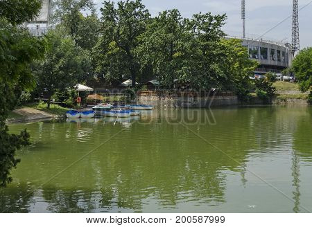 Cosy nook for summer relaxation with wooden pontoon and boat in lake Ariana, park  Borisova gradina, Sofia, Bulgaria