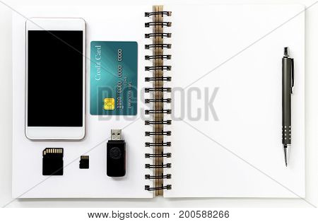 mobile phone credit card memory cards and ball pen on white note book. accessories of businessman and education.