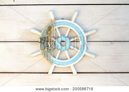 Wooden steering wheel on the white wall