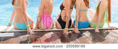 Back view of five young ladies, wearing colorful swim suits. Group of friends sitting on the side of the pool and having fun.Pool party, summer vacation. Banner for website