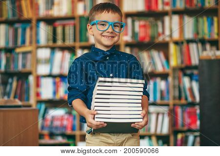 Boy With Glasses And Stack Of Books