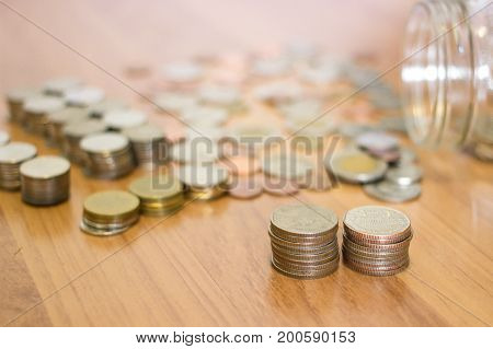 Row of 5-baht coin and Thai baht coin out of the glass jar background.