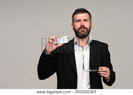 Man In Suit With Beard Holds White Business Card