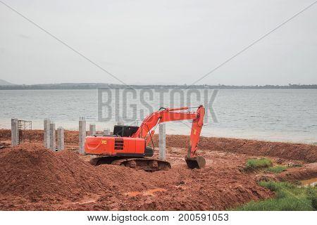 Backhoe loader digging soil on the shore.