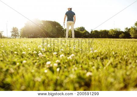 Male golfer holding golf club while standing at a green course