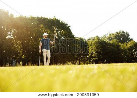 Young male golfer holding flag and a club while standing at a sunny green course