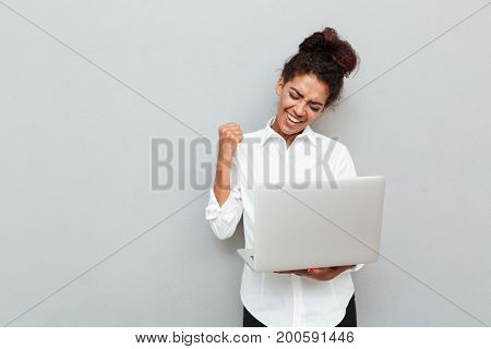 Photo of young african cheerful business woman standing over grey wall with laptop computer. Looking aside make winner gesture.