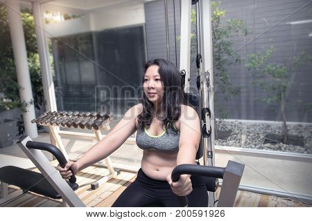 Fat woman bored tired face exercise weight loss on push arm machine give up workout concept