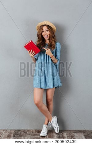 Image of happy young pretty woman standing over grey wall wearing hat reading a book. Looking camera.