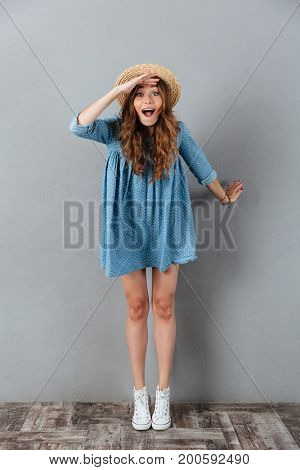 Picture of amazing young pretty woman standing over grey wall wearing hat. Looking camera.
