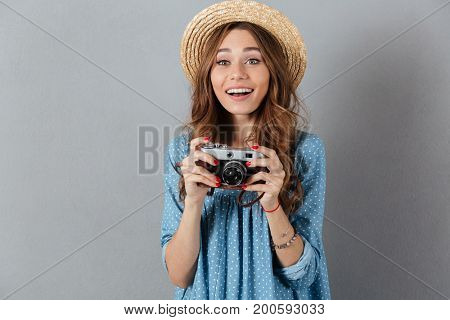Picture of smiling young caucasian woman photographer holding camera. Looking aside.