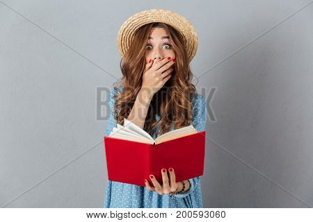 Picture of shocked young pretty woman standing over grey wall wearing hat reading a book. Looking camera.