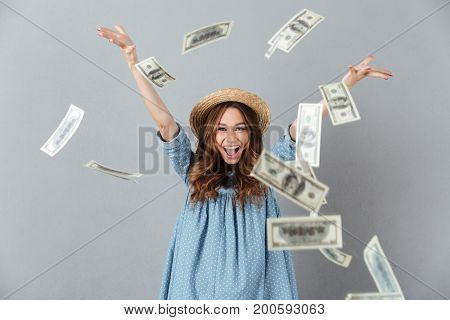 Image of cheerful young pretty woman standing over grey wall over money wearing hat.