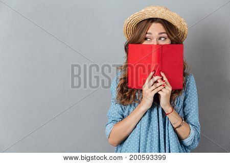 Picture of young pretty woman standing over grey wall wearing hat covering face with book. Looking aside.