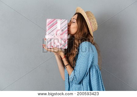 Image of surprised young pretty woman standing over grey wall wearing hat holding gift. Looking aside.