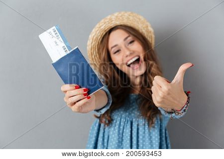 Image of happy young pretty woman standing over grey wall wearing hat holding passport and ticket showing thumbs up. Looking camera.