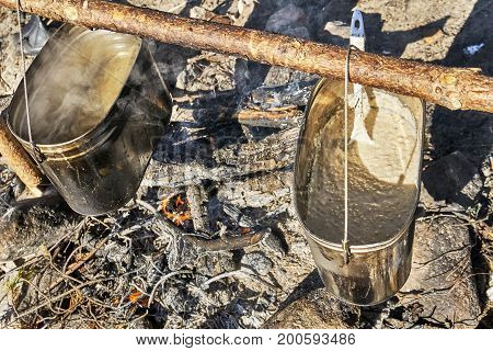 Preparing a porridge and tea on bonfire in a hike