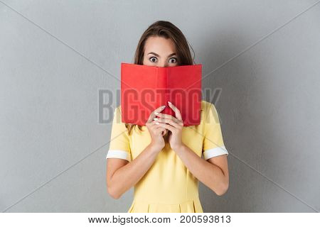 Surprised girl in dress covers her face with a book and looking at camera isolated over gray background