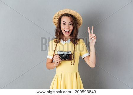 Happy young girl in hat holding retro camera and showing peace gesture while standing isolated over gray background