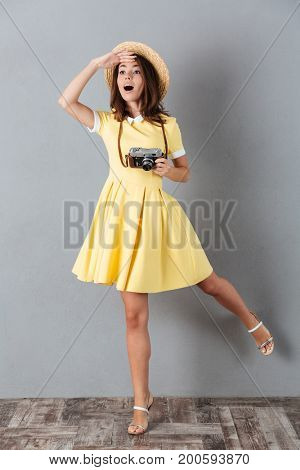 Lovely pretty girl in hat posing on one leg and looking far away while holding retro camera isolated over gray background