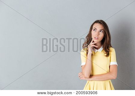 Portrait of a thoughtful young girl standing and looking away at copy space isolated over gray background
