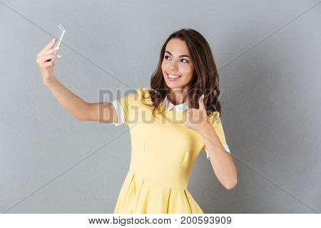 Smiling young girl showing thumbs up gesture while taking a selfie with mobile phone isolated over gray background