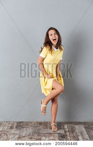 Full length portrait of an excited young girl in dress dancing and having fun isolated over gray background
