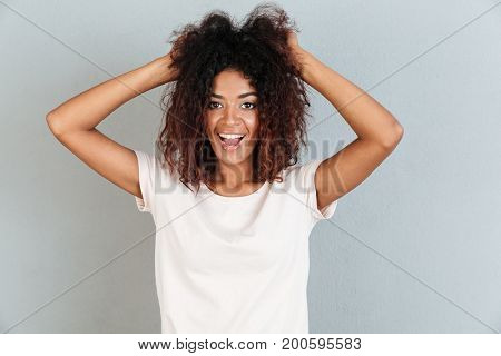 Happy casual african woman laughing and playing with her hair while standing isolated over white background