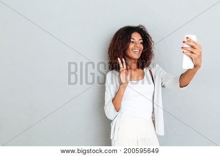 Smiling attractive african woman showing peace gesture and taking a selfie while standing isolated over white background
