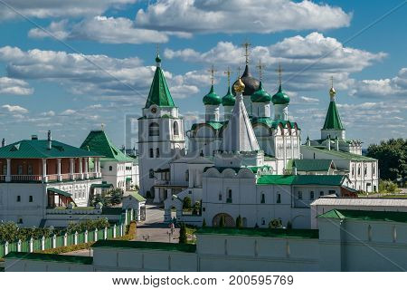View at Pechersky ascension monastery white clear Sunny day. Is a Church with a bell tower and gold domes. The monastery is surrounded by white stone walls. In the sky floating Cumulus clouds.