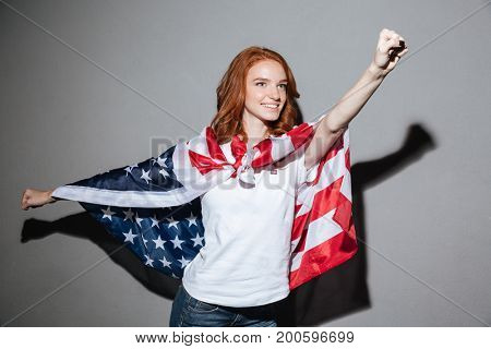 Image of amazing redhead young lady superhero with USA flag. Looking aside.