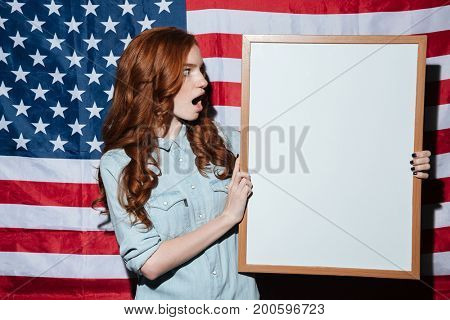 Photo of confused redhead young lady holding copyspace board over USA flag. Looking aside.
