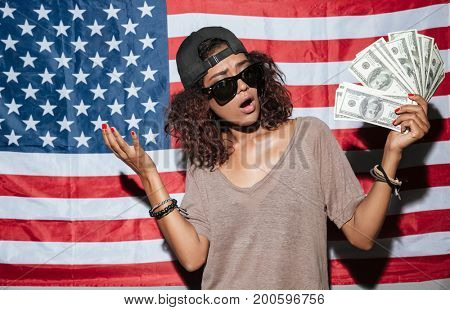 Image of serious african young woman with money standing over USA flag. Looking aside.