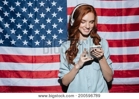 Image of happy redhead young lady listening music and chatting over USA flag. Looking aside.