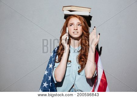 Image of confused redhead young lady holding book on head wearing USA flag. Looking aside talking by phone.