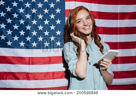 Picture of cheerful redhead young lady listening music and chatting over USA flag. Looking camera.