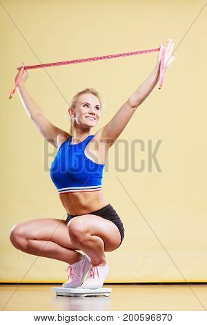 Slimming diet weight loss. Joyful female standing on bathroom scales arms up holds measure tape celebrating success