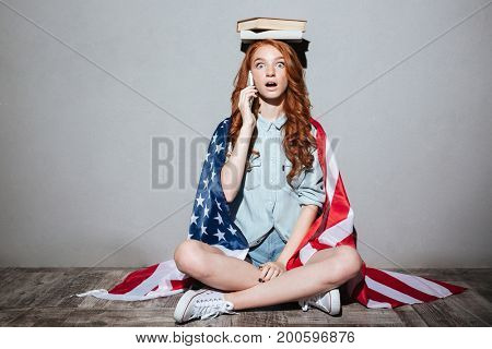 Image of shocked redhead young lady holding book on head wearing USA flag. Looking camera talking by phone.