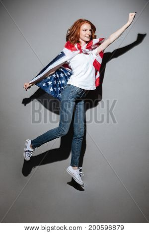 Photo of amazing redhead young lady superhero with USA flag. Looking aside.