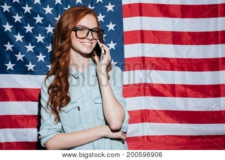 Photo of cheerful redhead young lady standing over USA flag. Looking aside talking by phone.
