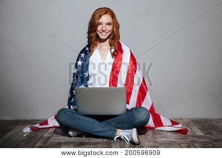 Picture of happy redhead young lady with USA flag using laptop computer. Looking camera.