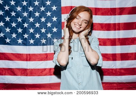 Image of happy redhead young lady listening music over USA flag. Eyes closed.
