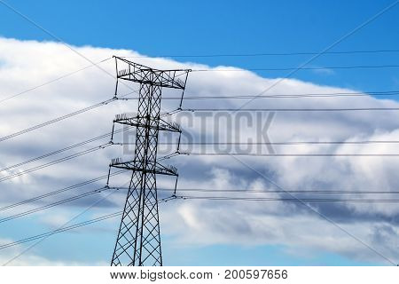Overhead Electricity Pylon And Cables Against Blue Cloudy Skyline