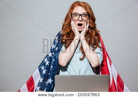 Image of shocked redhead young lady with USA flag using laptop computer. Looking camera.