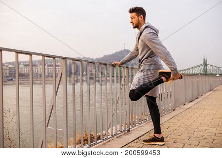A handsome young man holding the fence and stretching his leg at the riverside